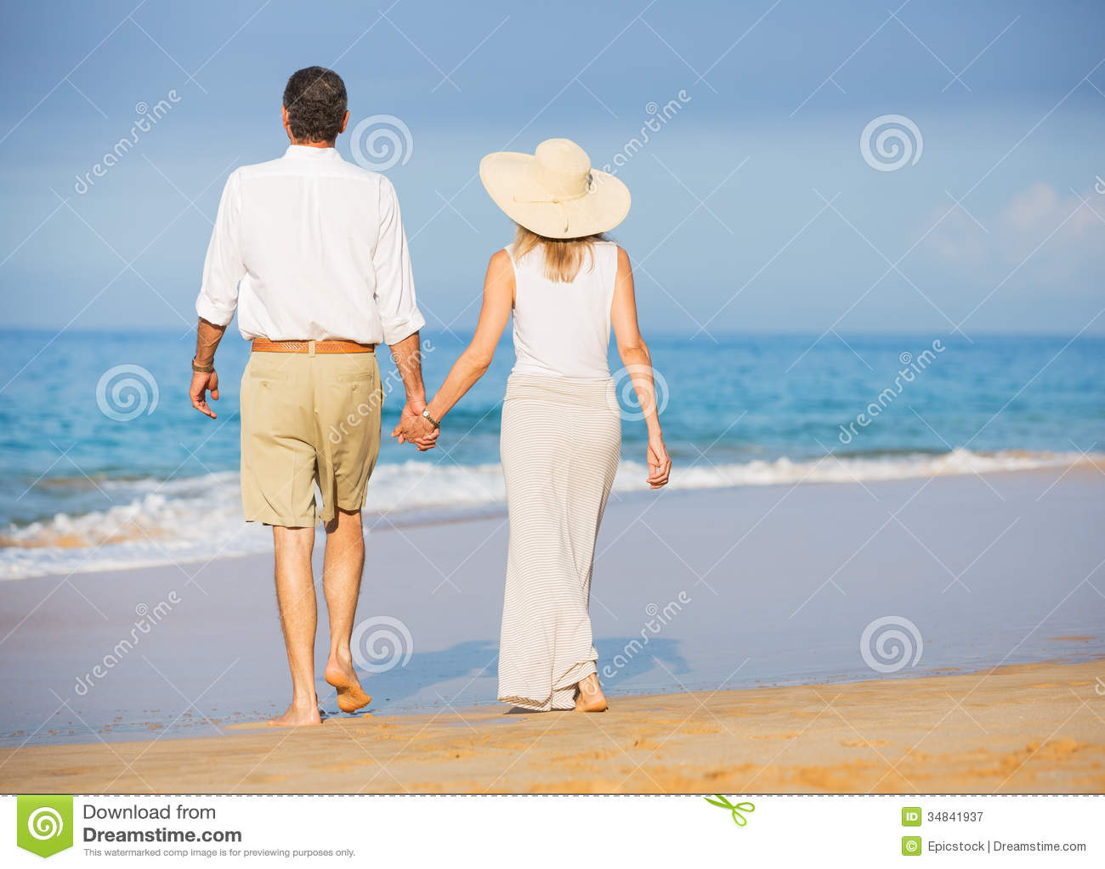 Pares superiores felizes na praia. Aposentadoria Res tropical luxuoso