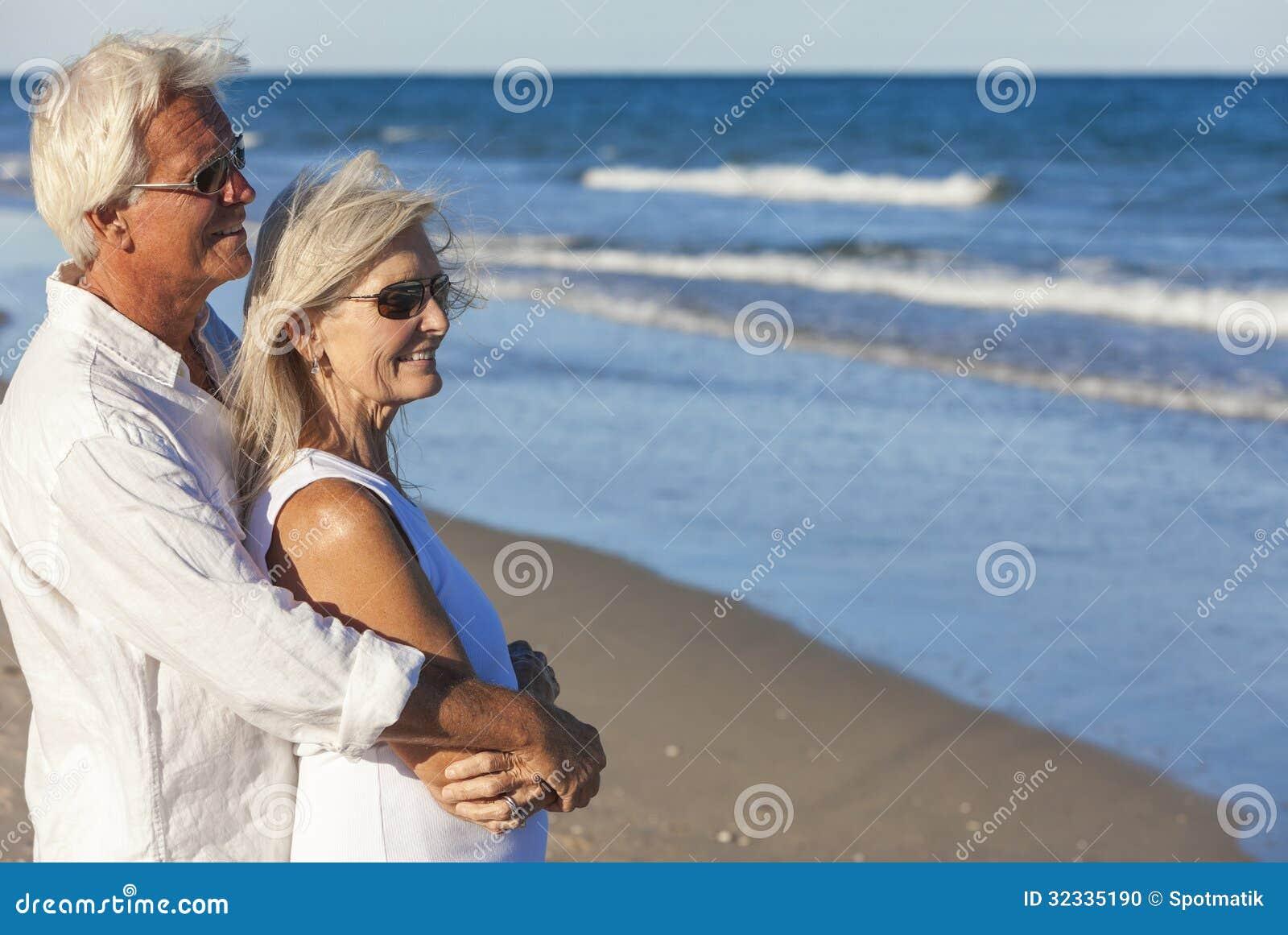 Pares superiores felizes que olham ao mar em uma praia tropical