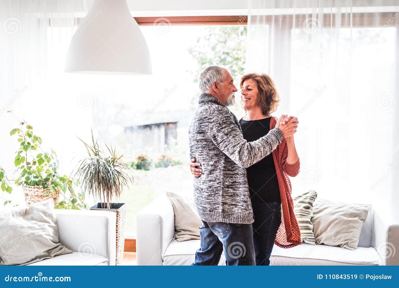 Pares superiores que relaxam em casa, dançando