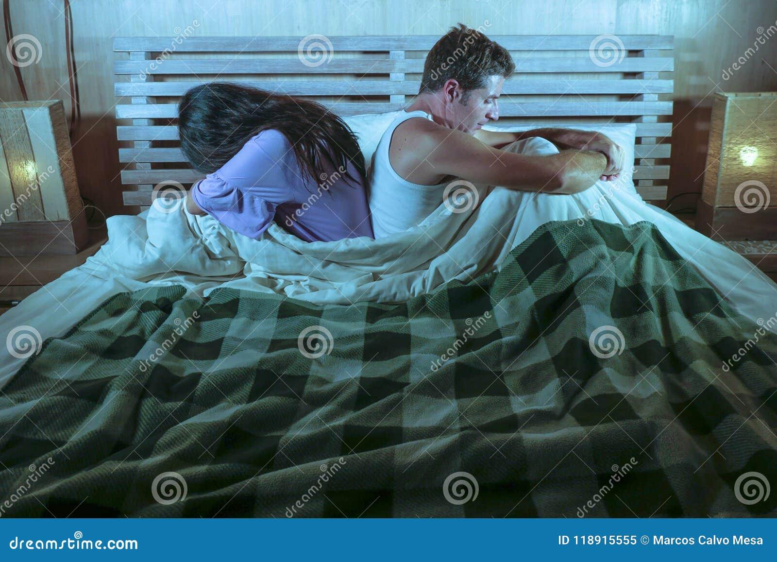 Pares tristes após a luta doméstica com o grito deprimido da mulher e o noivo frustrante que sentam-se na cama infeliz no esforço