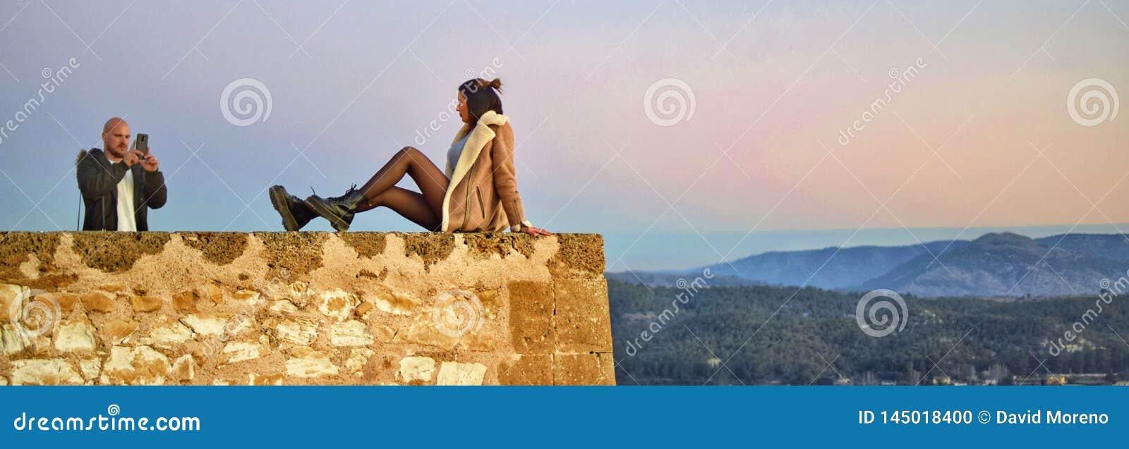 Pares turísticos que toman la foto en el precipicio del castillo en España de Caravaca