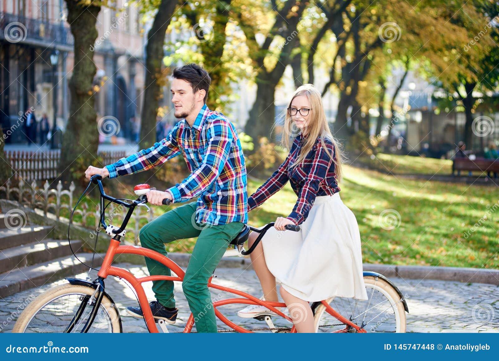 Pares tur?sticos jovenes, hombre hermoso y mujer bastante rubia montando la bicicleta en t?ndem a lo largo de la calle de la ciud