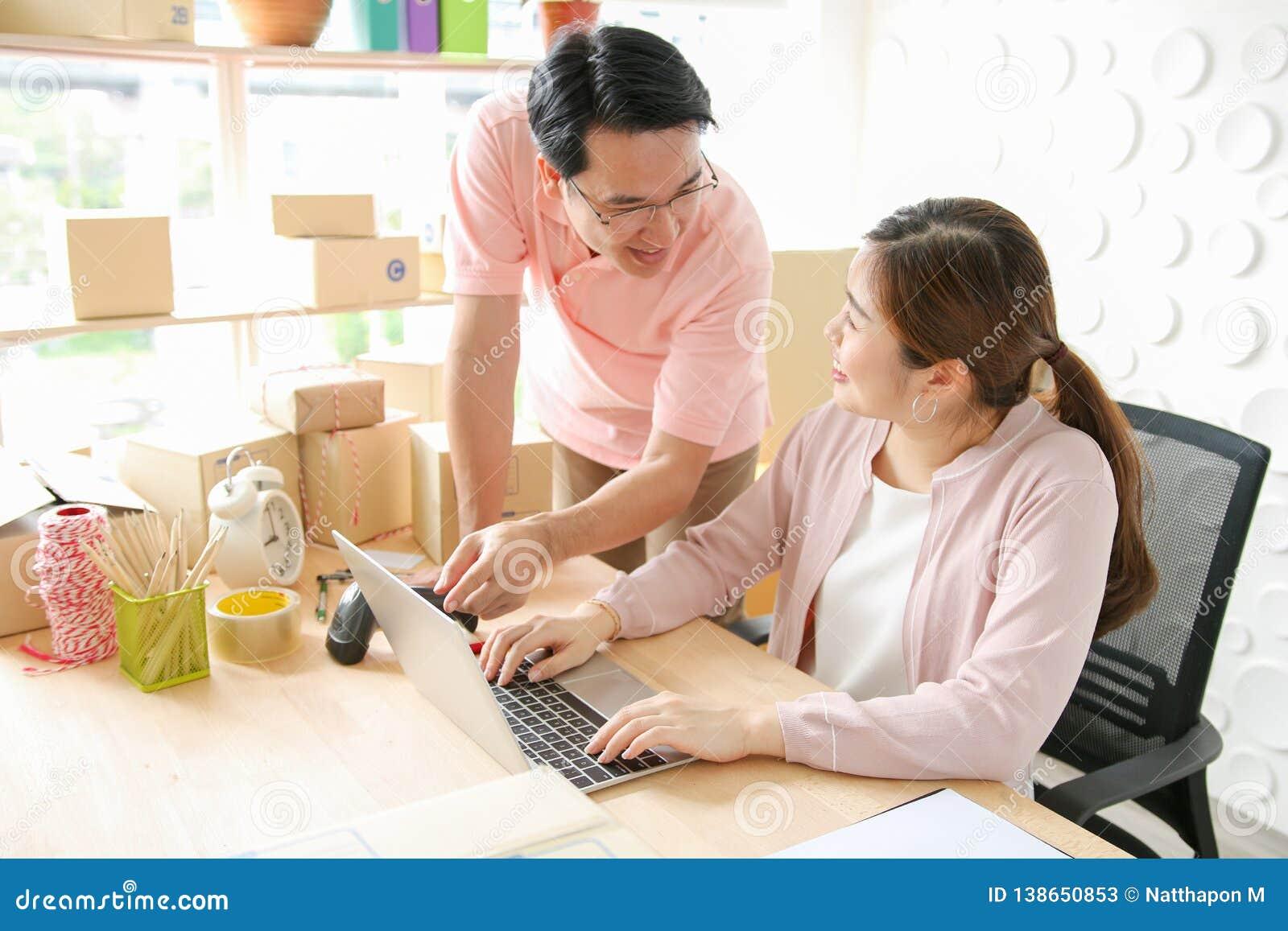 Pares usando o portátil em casa Apontar na tela com felizmente SME, ordem do produto da verificação, vendendo em linha, comércio