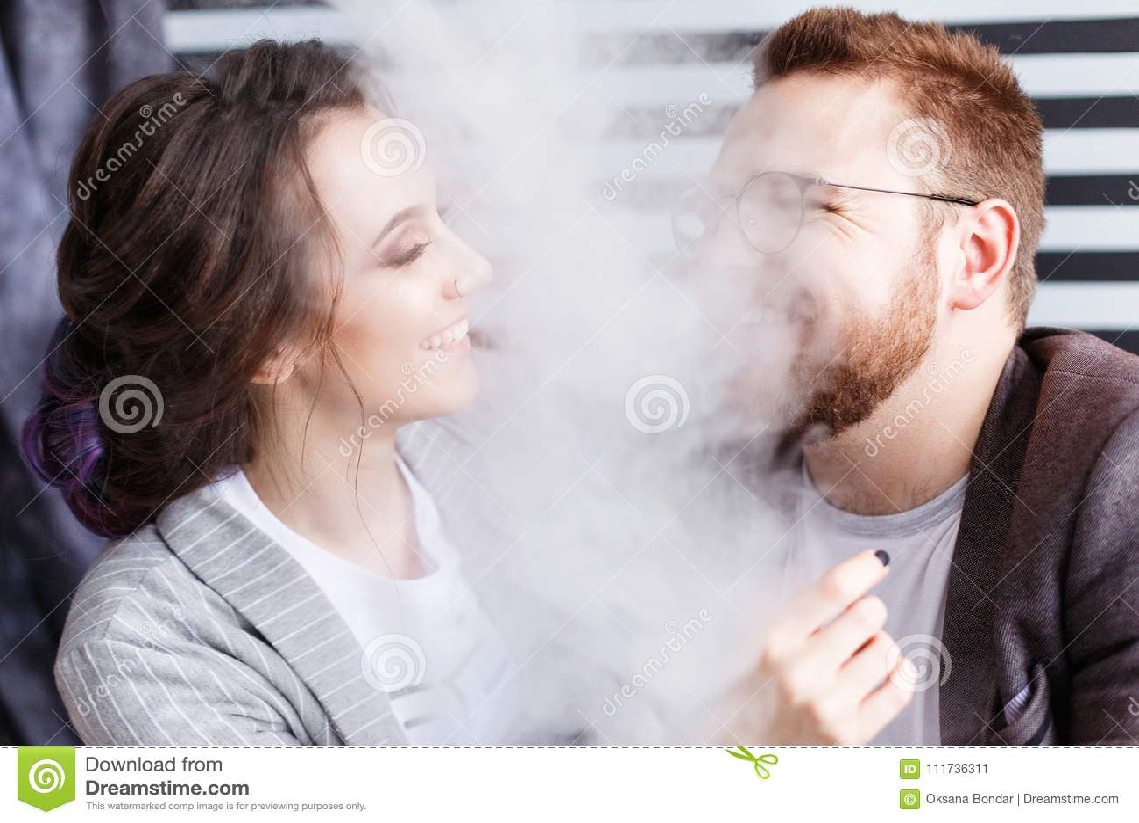 Pares vaping Humo que sopla del hombre joven y de la mujer en el fondo rayado blanco y negro del estudio Relación y vape