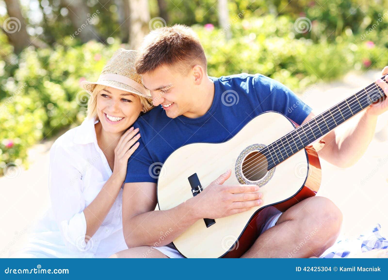 Pares y guitarra románticos en la playa