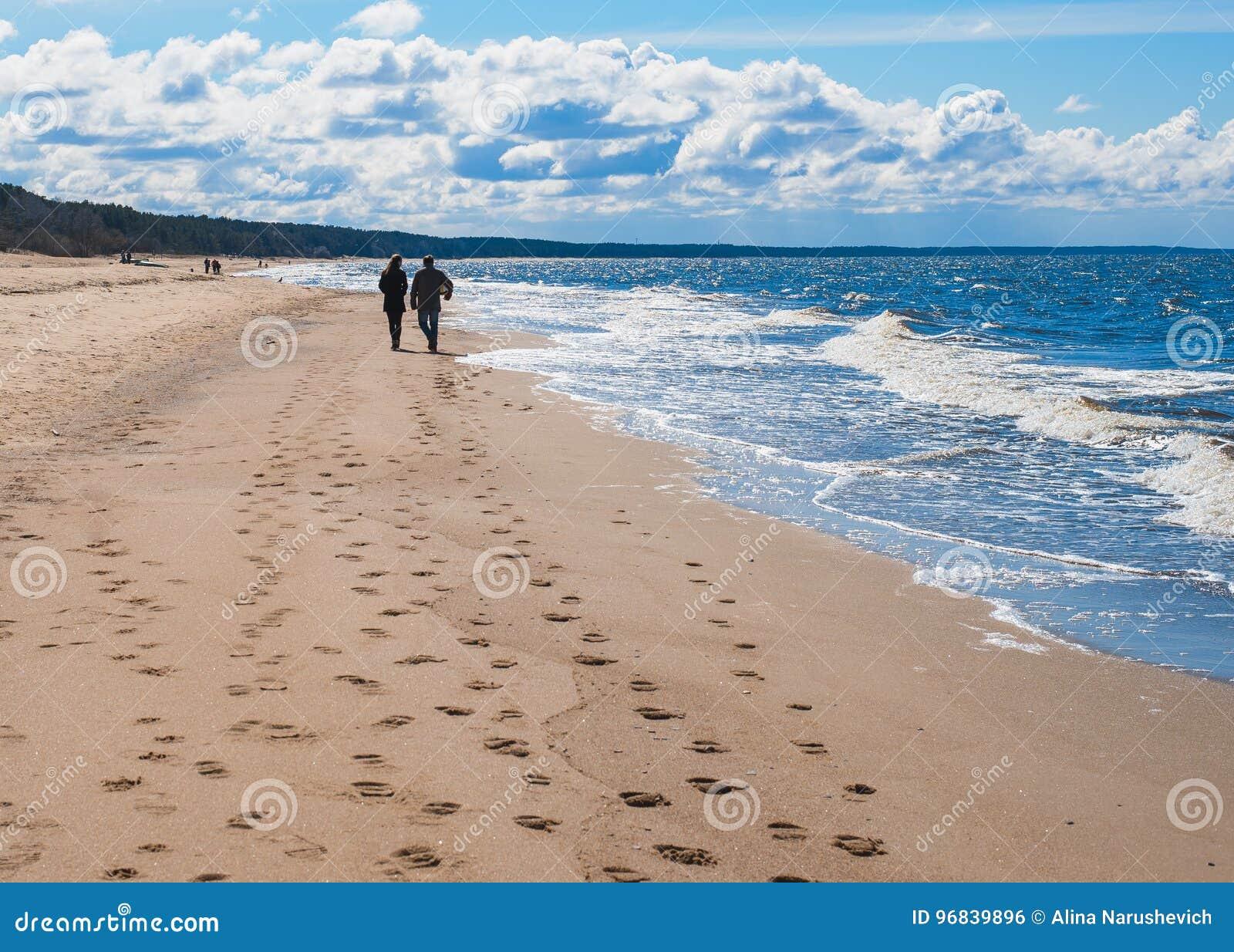 Paret promenerar stranden under blå himmel