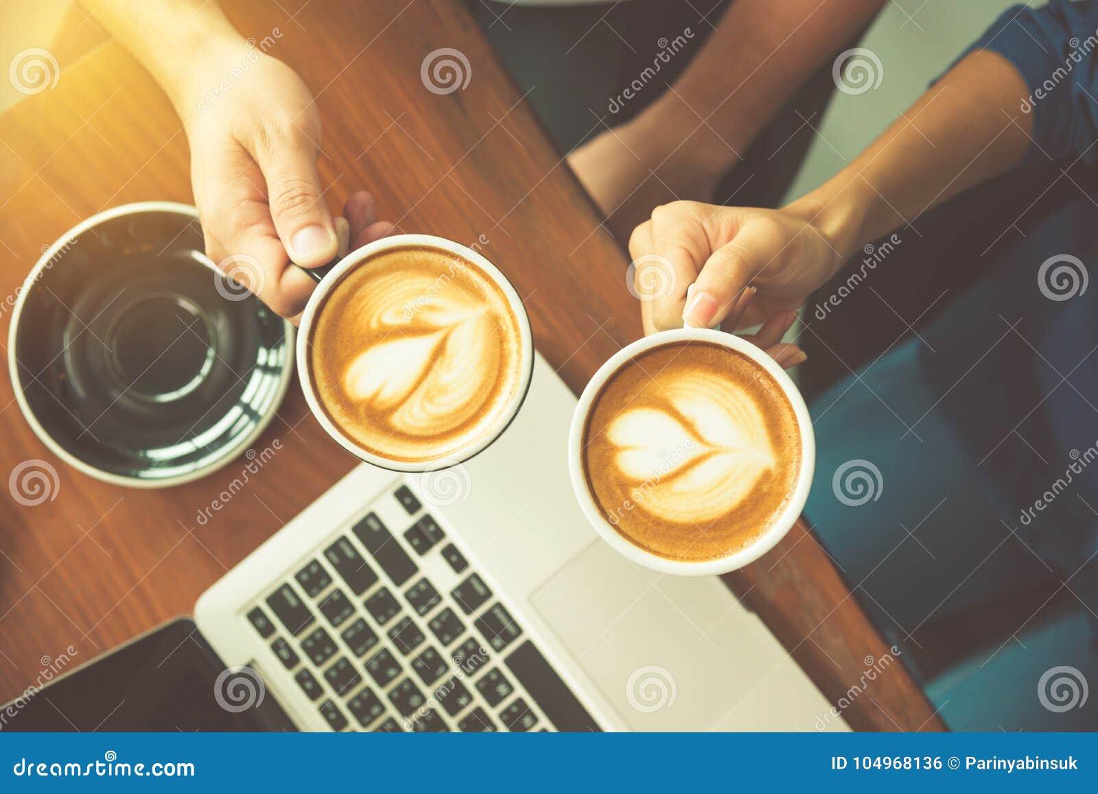 Paret räcker den hållande kaffekoppen på det funktionsdugliga skrivbordet med bärbara datorn