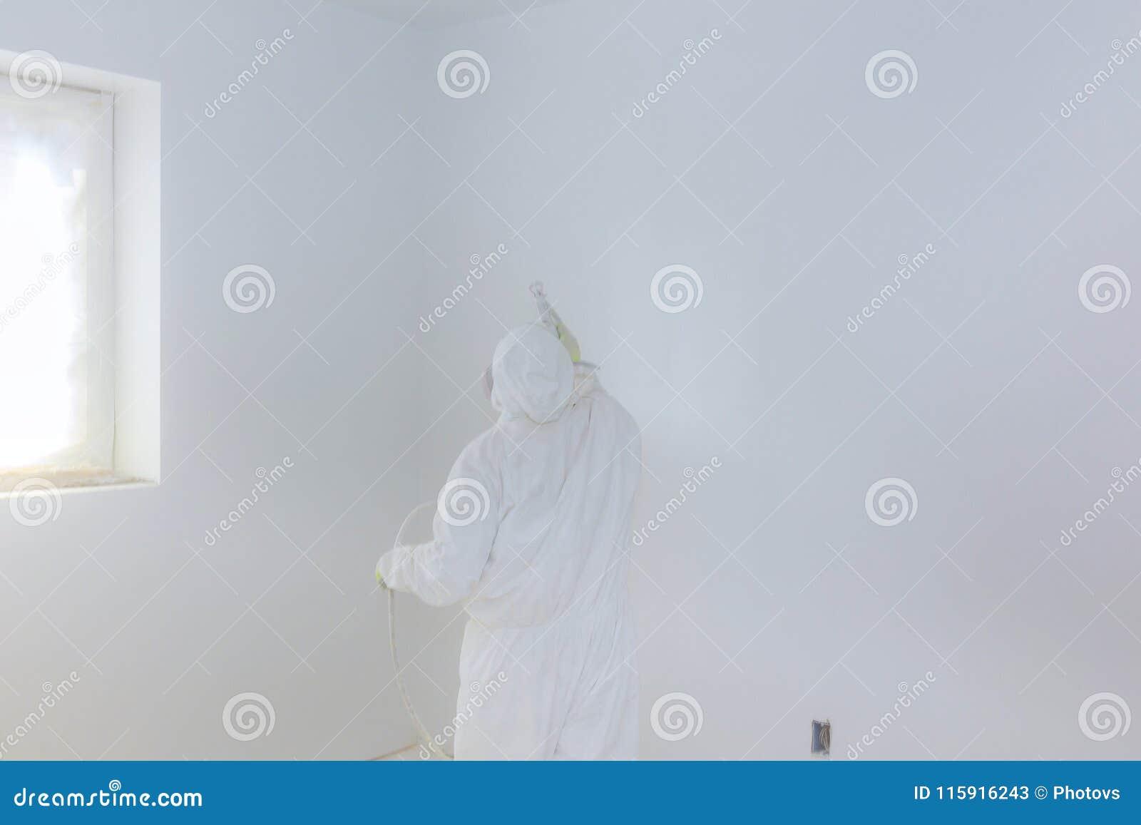 Parete della pittura del lavoratore con la pistola a spruzzo nel colore bianco