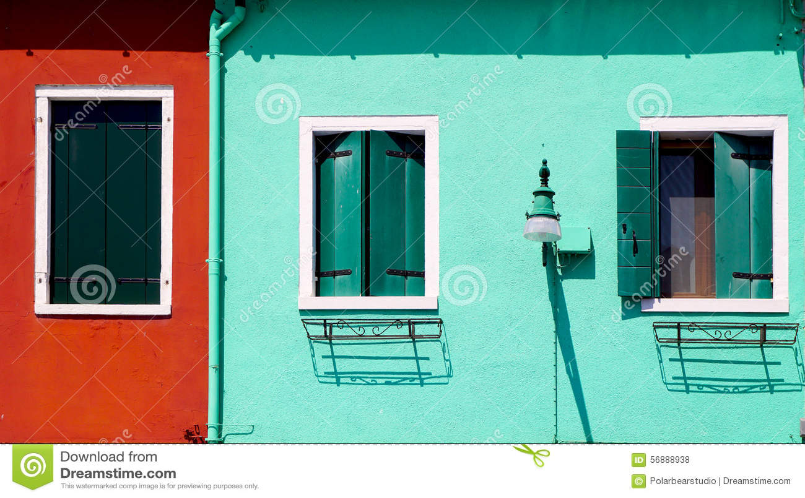 Parete rossa e verde con la casa delle finestre