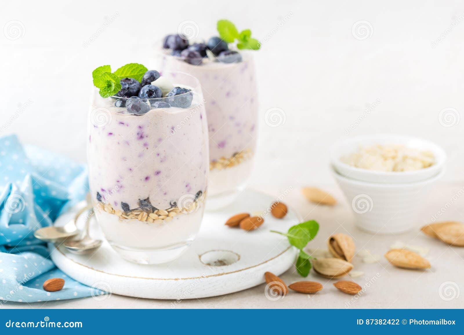 Parfait grec à yaourt ou à myrtille avec les baies et les écrous frais d amande sur le fond blanc