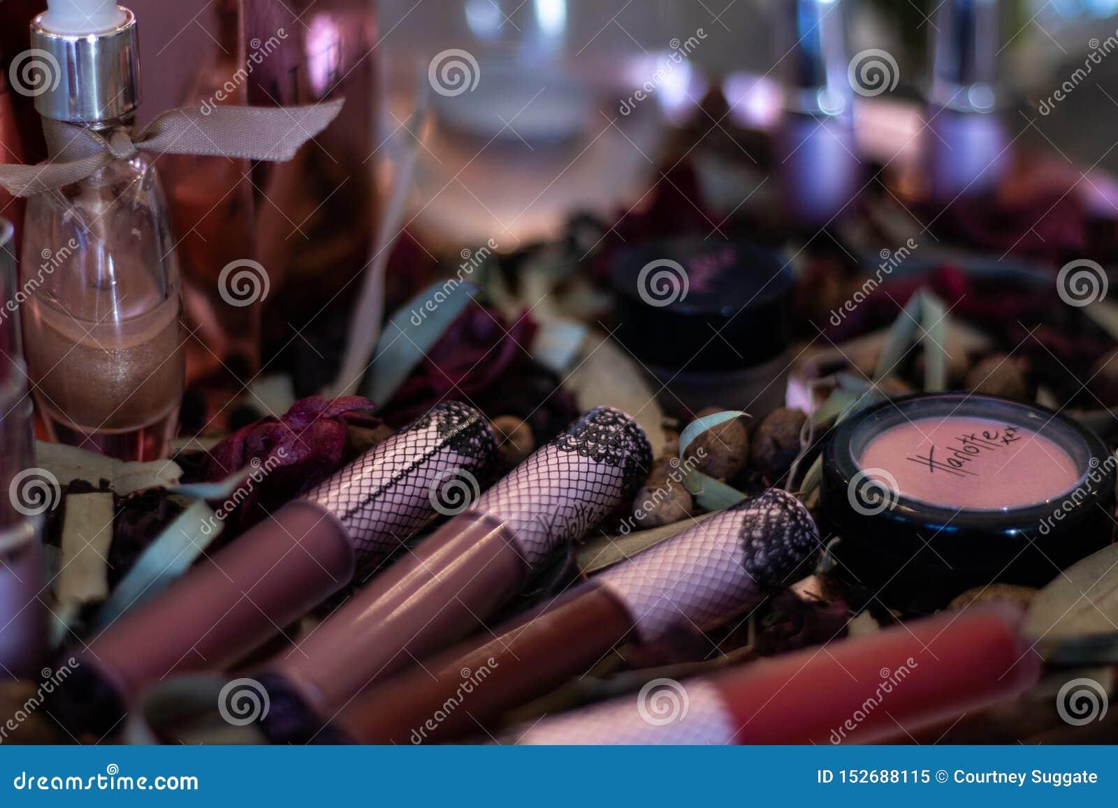 Parfum assorti de rouge à lèvres de produits de beauté sur le lit des pétales