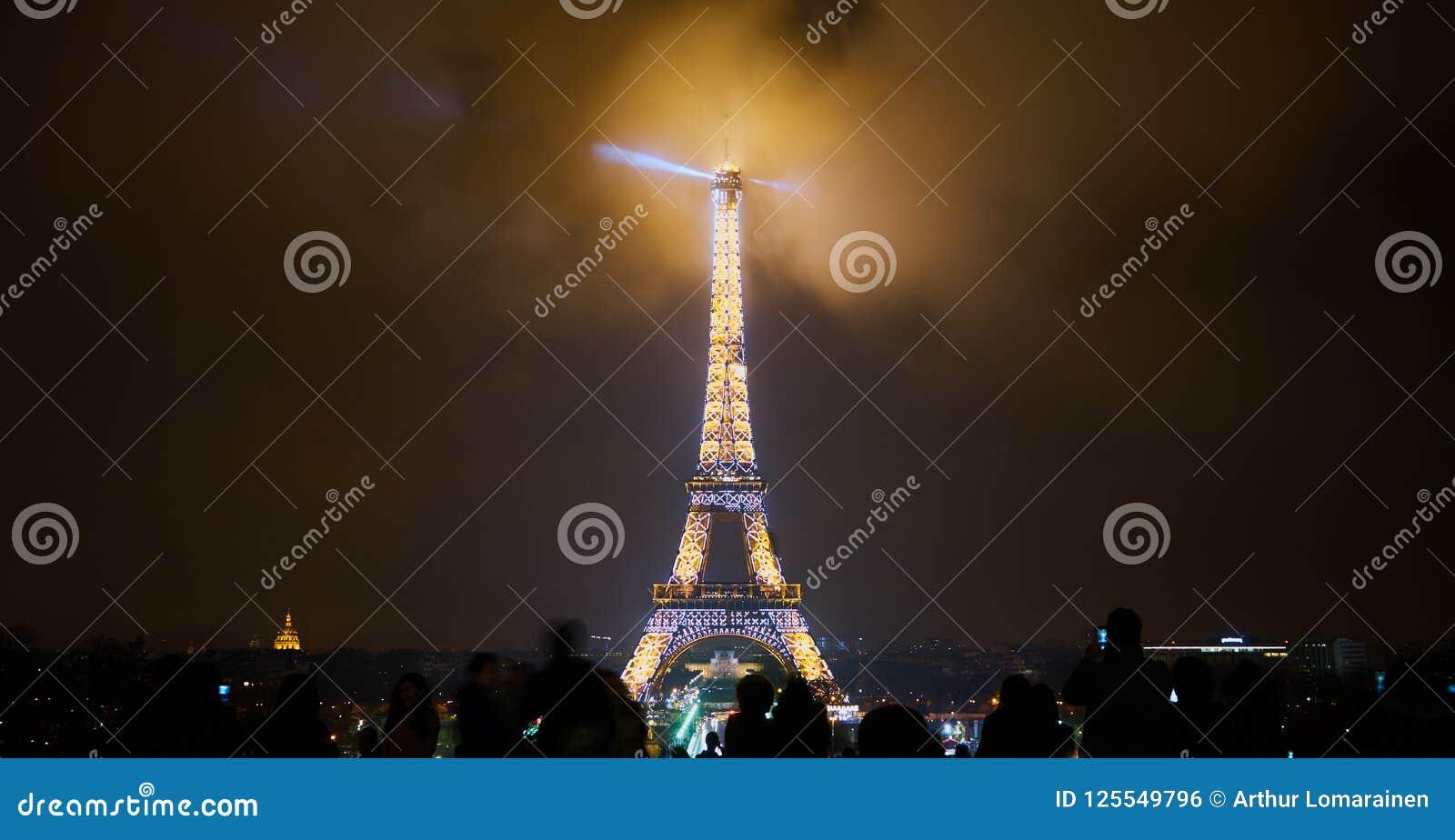 Parigi, Francia - 23 dicembre 2017: La gente sta esaminando la torre Eiffel illuminata alla notte