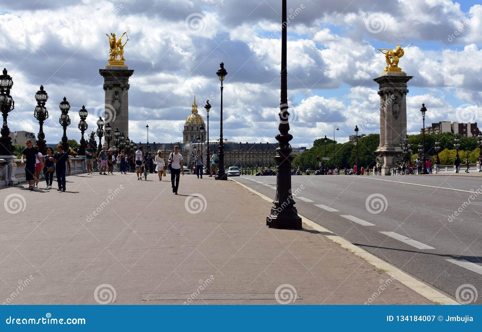 Parijs, Frankrijk Alexandre III Brug en Invalides met toeristen Kolommen, standbeelden en straatlantaarns, regenachtige dag