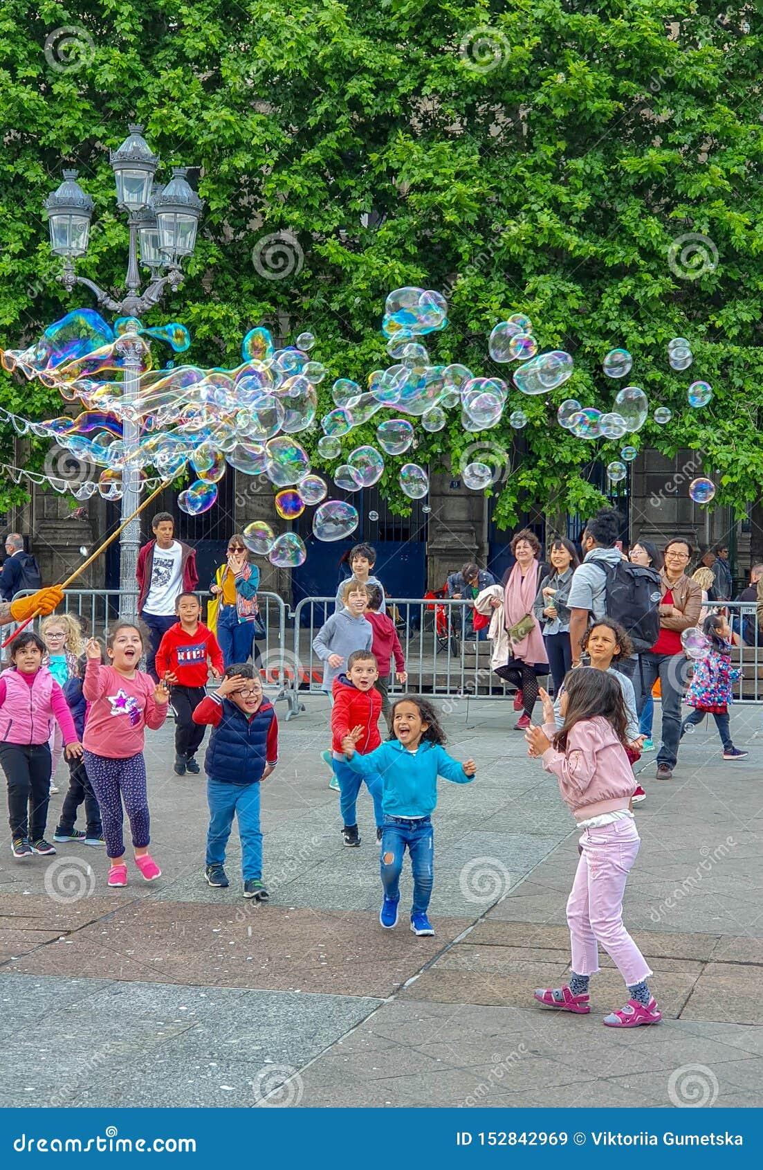 Parijs, Frankrijk, Juni 2019: De kinderen die van bellen genieten tonen op de Plaats DE l 'Hotel DE Ville