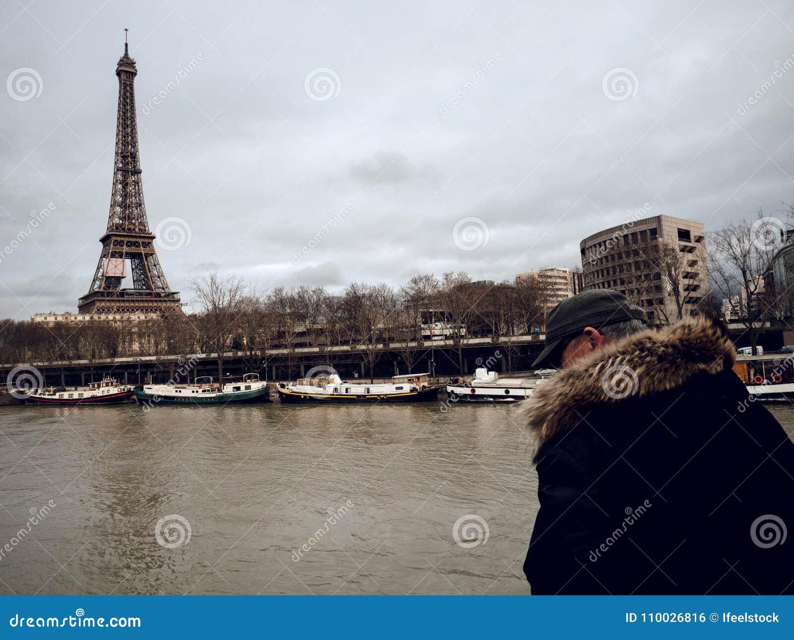 Parijse Franse mens die op de overstromende gezwelde Zegenrivier letten