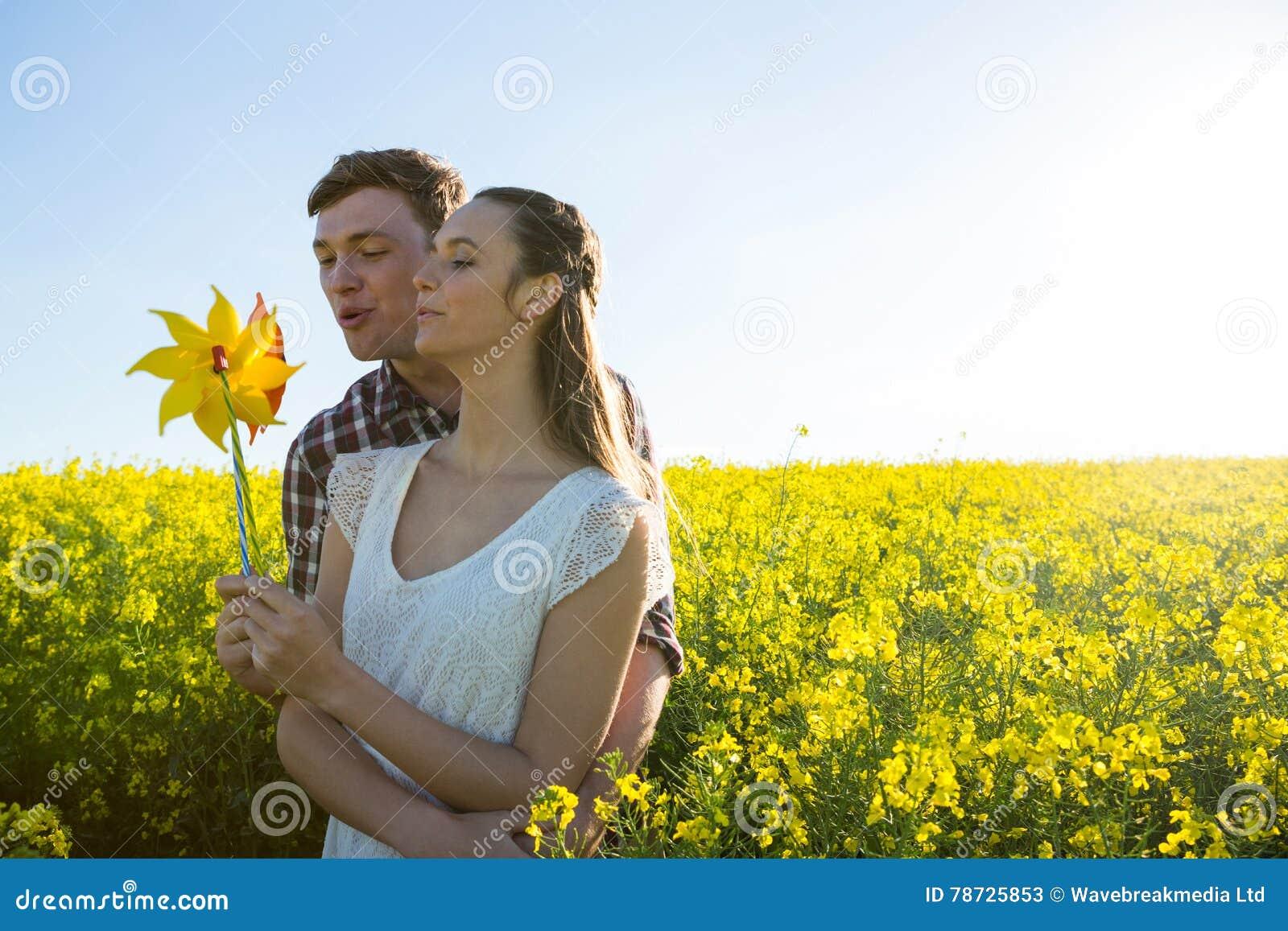 Parinnehav som blåser lilla solen i senapsgult fält