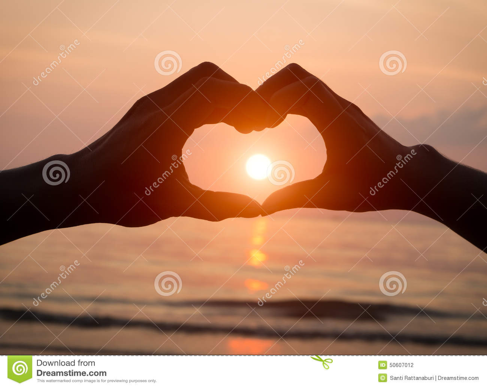 Parinnehavet räcker hjärtaförälskelse på solnedgången på stranden