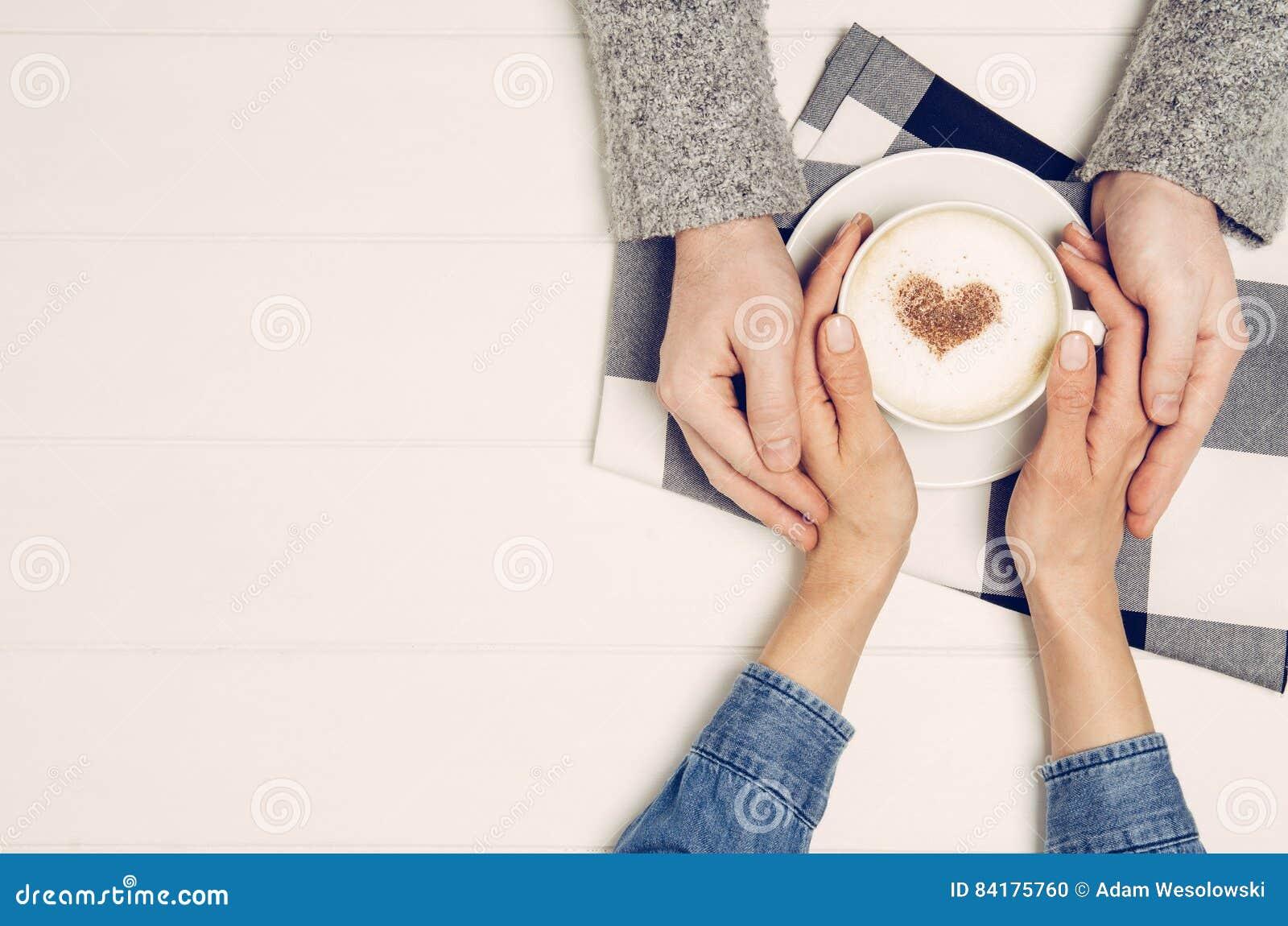 Parinnehavhänder med kaffe på den vita tabellen, bästa sikt