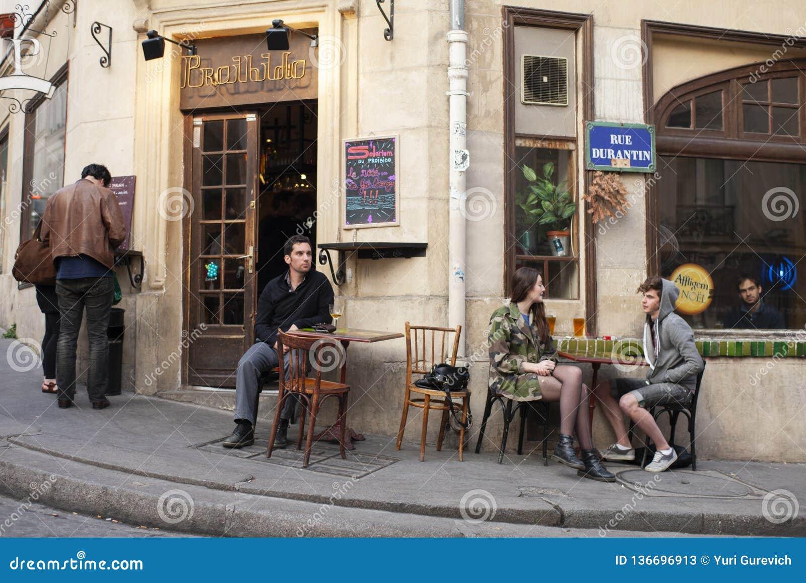 Paris, França - 11 de abril de 2011: amigos felizes que falam no café do verão, ar livre urbano
