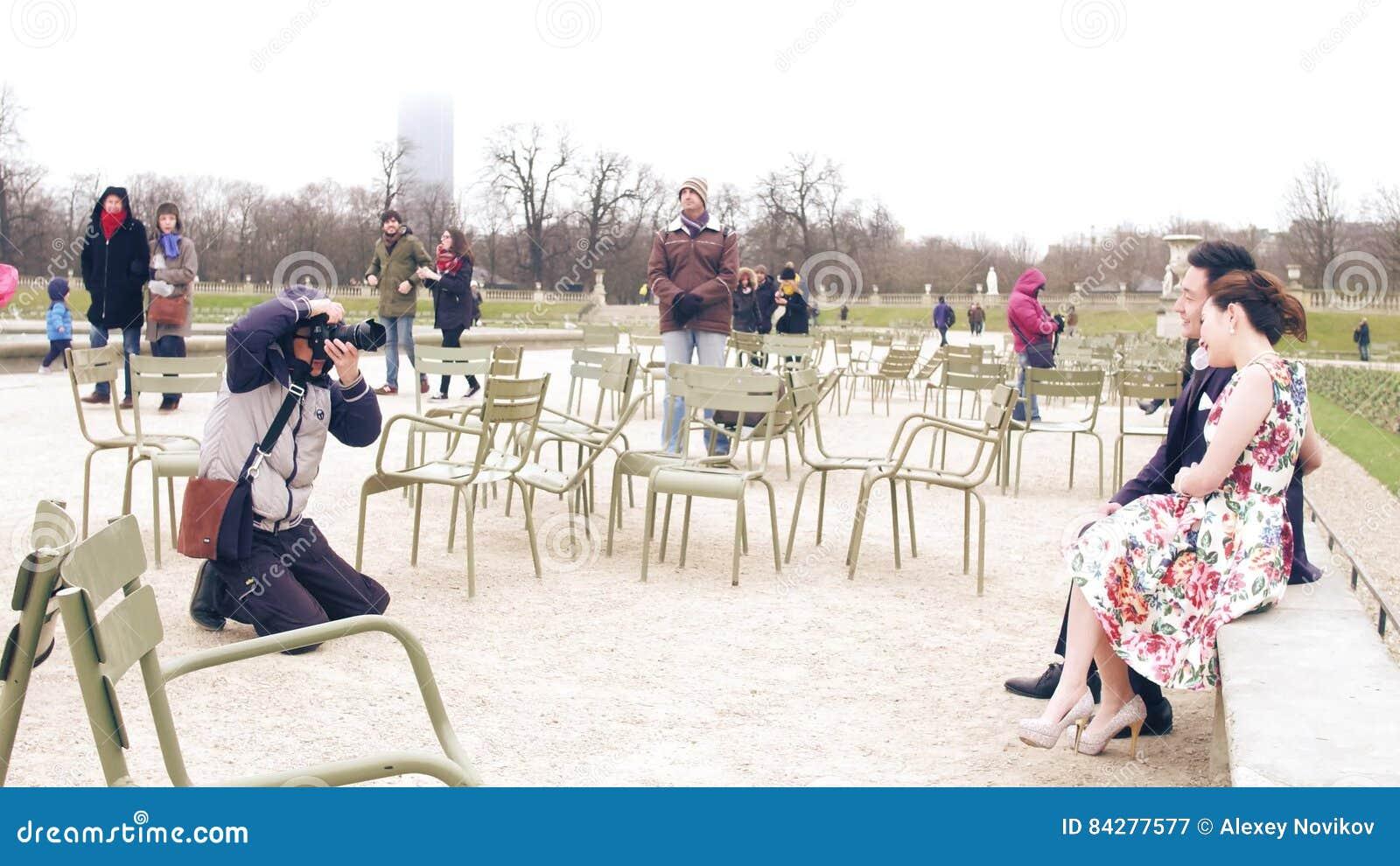 PARIS, FRANÇA - DEZEMBRO, 31, 2016 Fotógrafo asiático do casamento no trabalho Pares chineses que levantam no parque parisiense