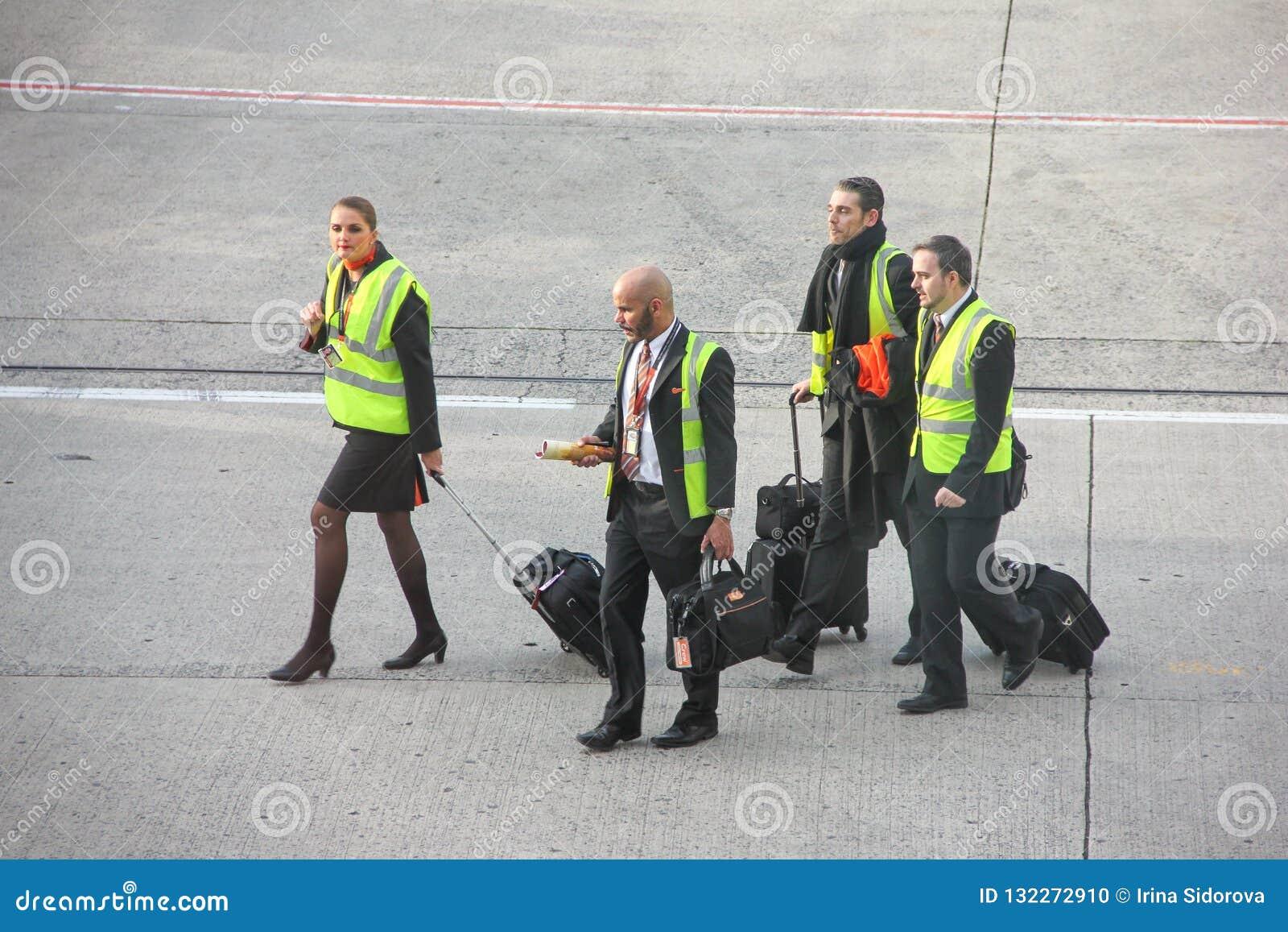 Paris, França - em abril de 2016: Grupo de grupo EasyJet da cabine que anda na pista de decolagem dos aeródromos em Charles de Ga