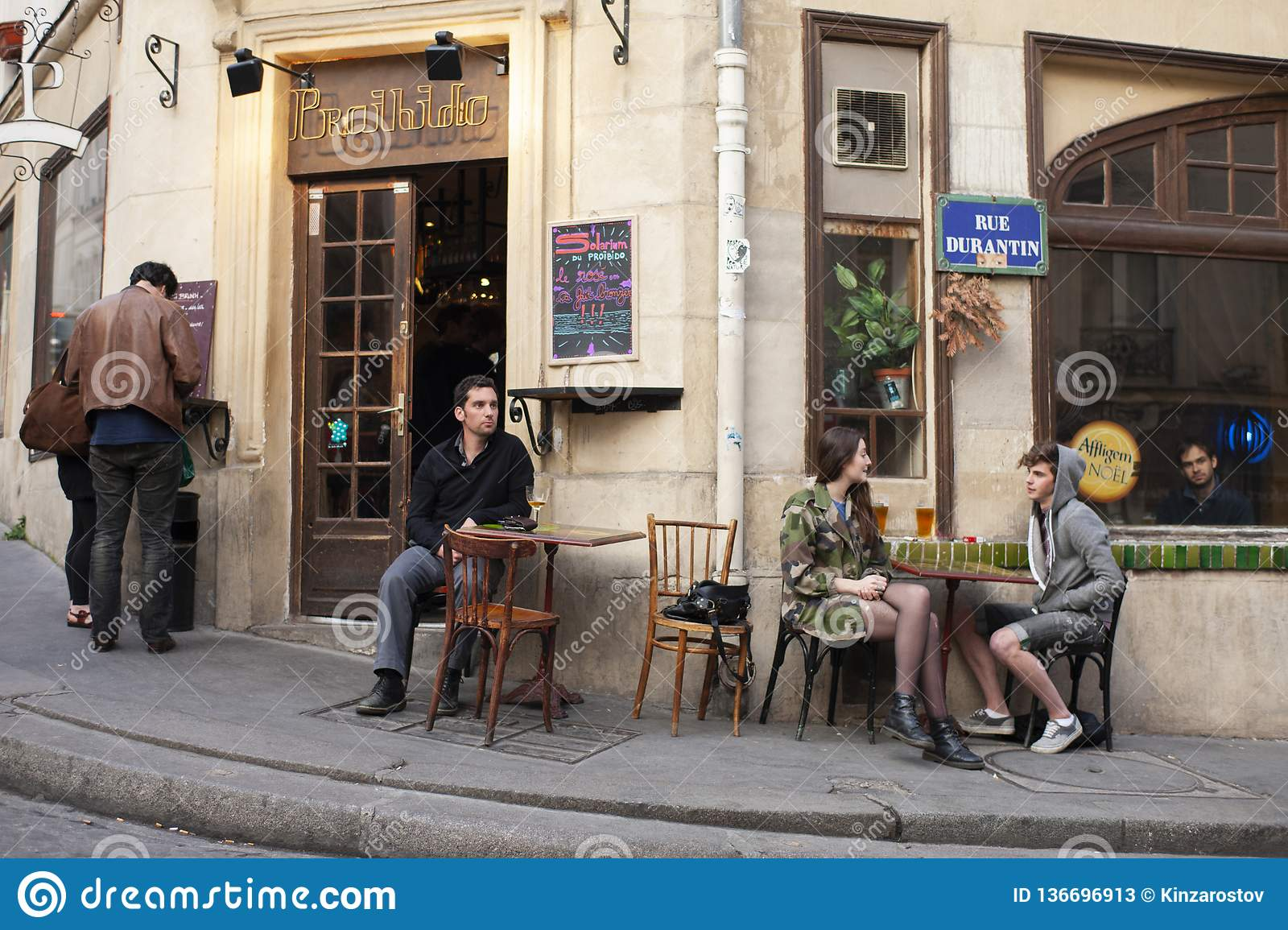 Paris, France - April 11, 2011: happy friends talking in summer cafe, urban outdoors