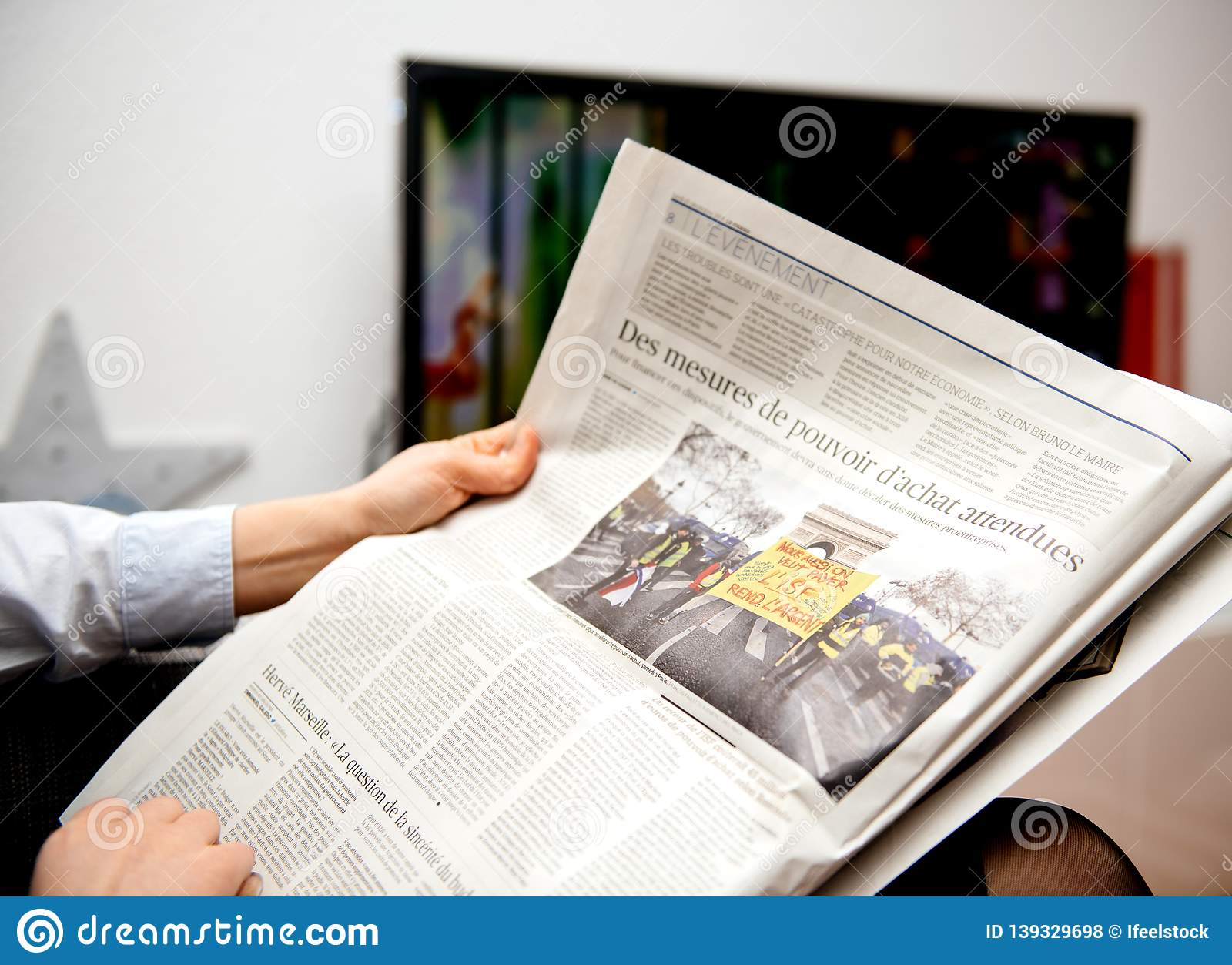 Woman reading french le figaro newspaper editorial stock photo
