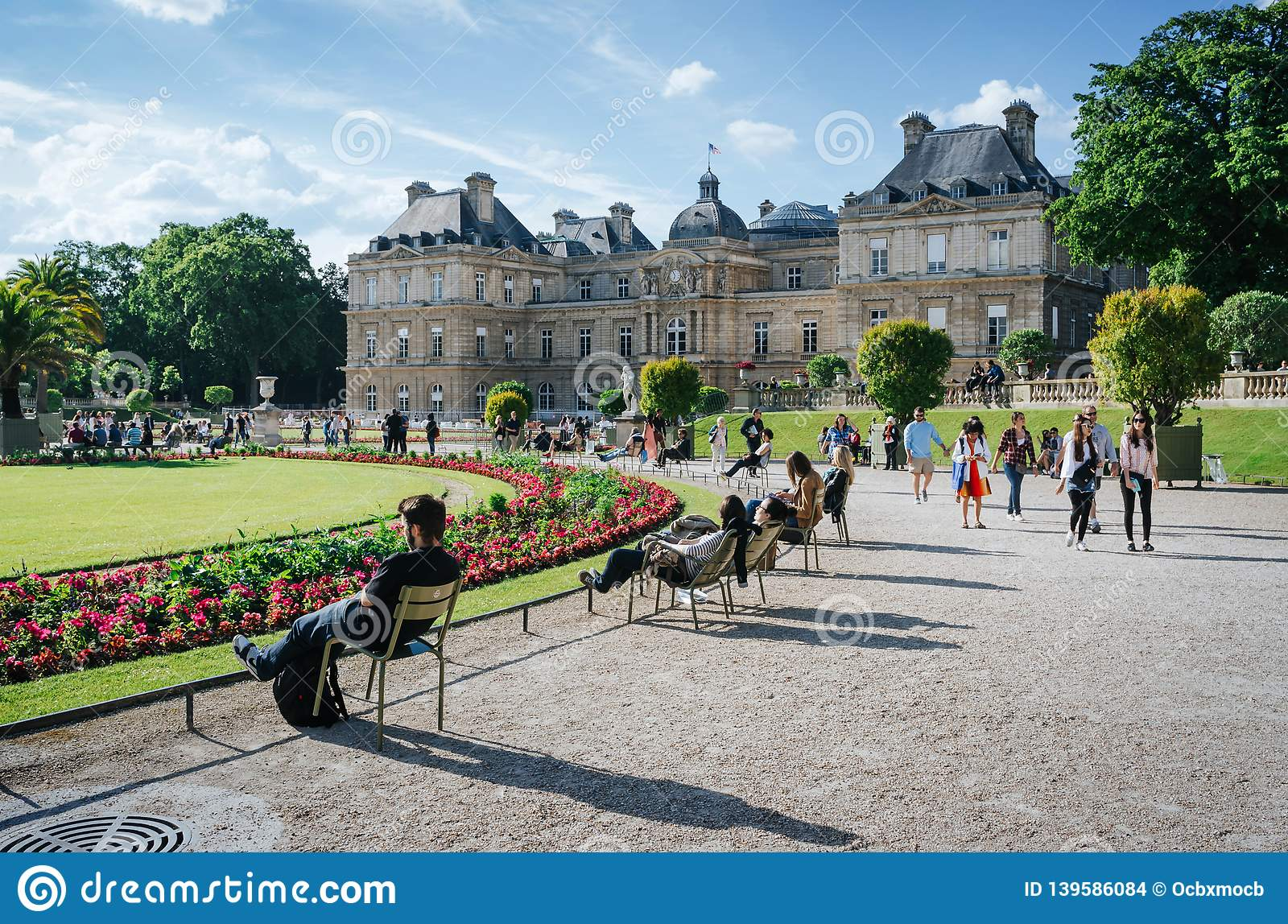 PARIS, FRANCE - JUNE 26, 2016: People relax and hang out in pucturesque park in front of Palais du Luxembourg or Luxemburg Palace