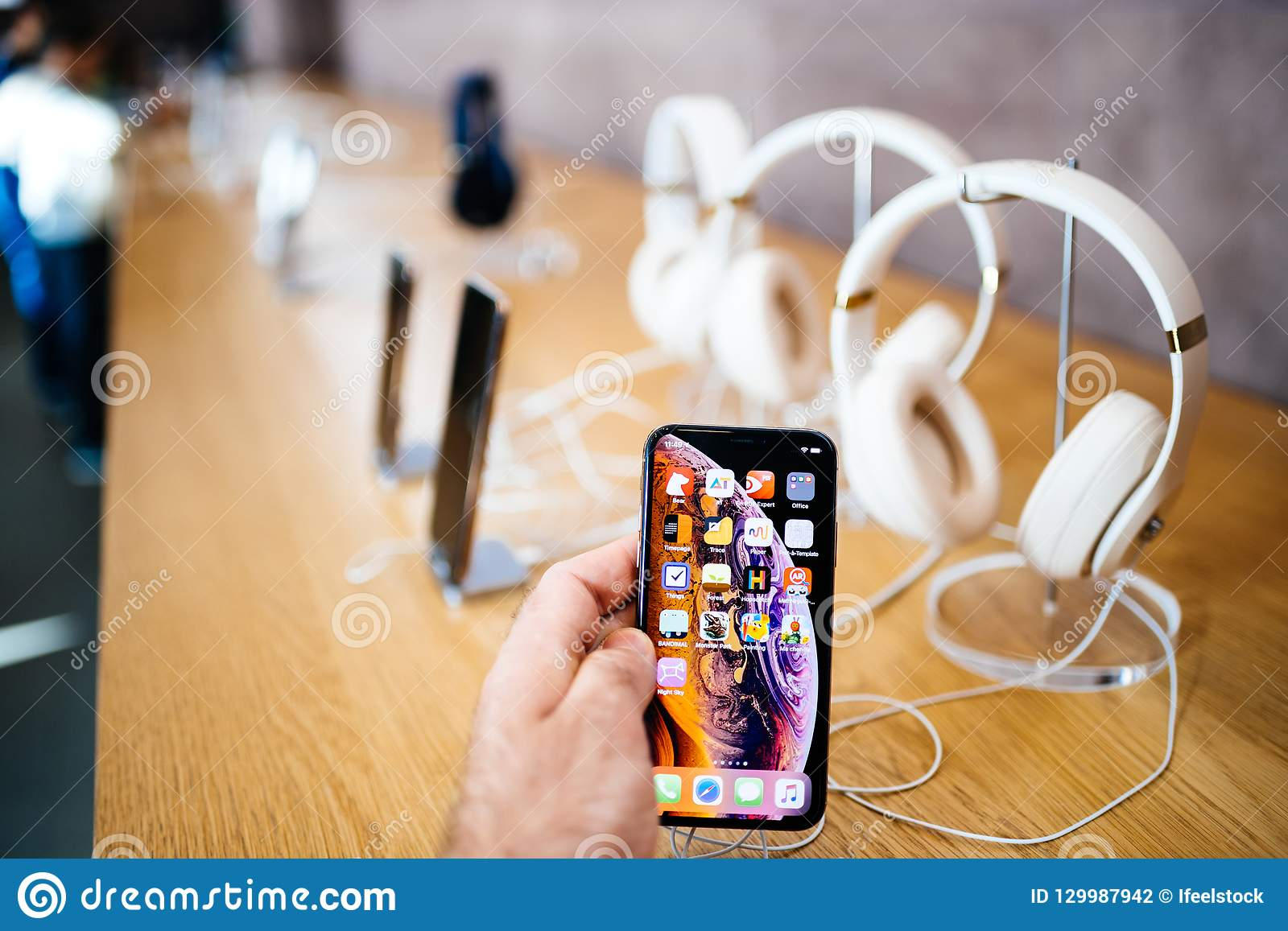 9e5af78cfe6 PARIS, FRANCE - OCT 26, 2018: Man hand holding new iphone Xs Xr Max with  Apple Music app and multiple wireless bluetooth headphones Beats By Dr Dre  Studio 3