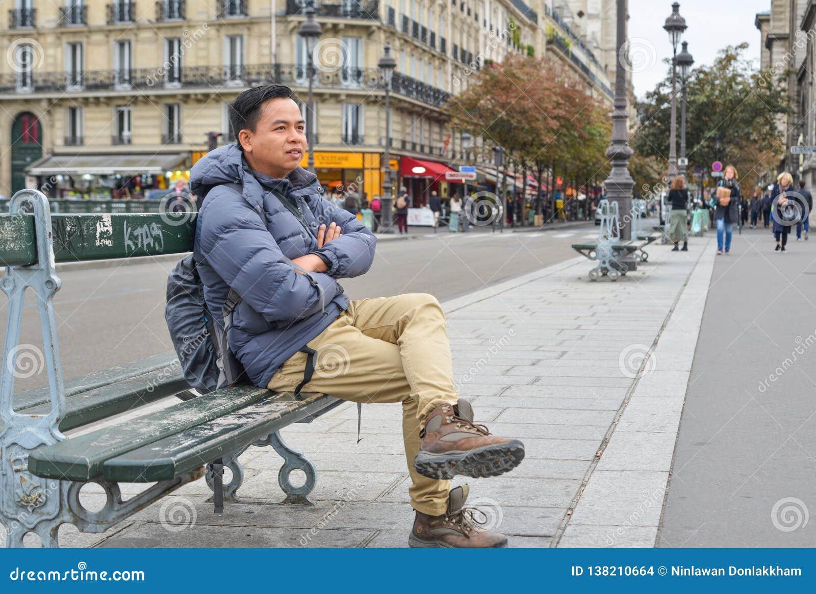 A man sitting on vintage bench