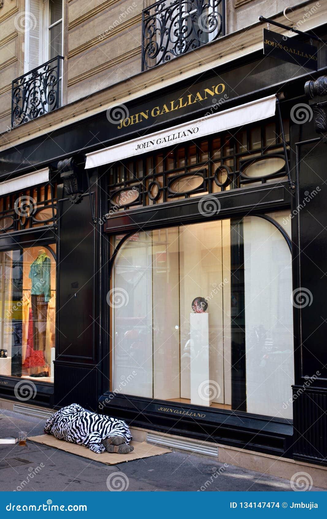 Paris, France Uns sem abrigo dormem em caixas na frente de um boutique luxuoso no quarto de Marais