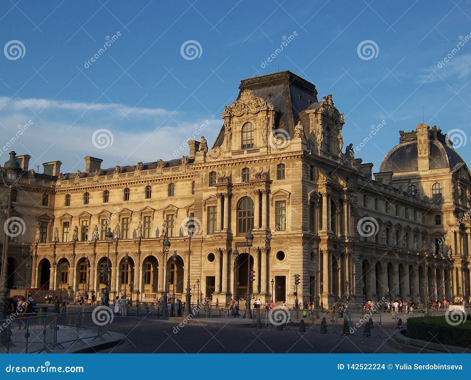 Paris Frankrike-Augusti 05, 2009: Härlig gammal arkitektur av Louvre som bygger på solnedgången på en sommarafton