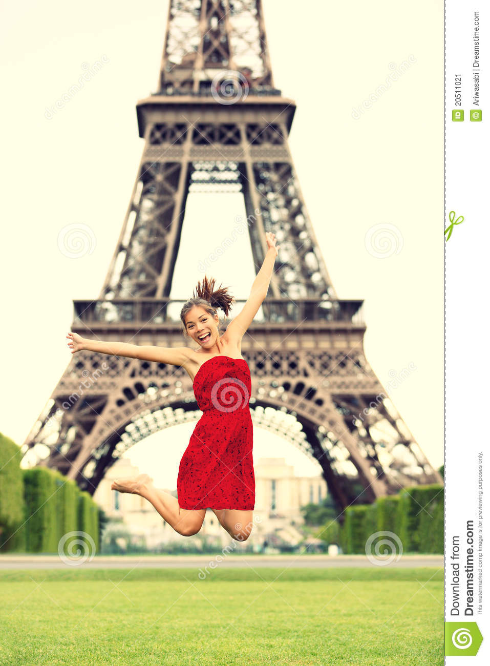 Paris girl at eiffel tower jumping happy smiling excited in red summer