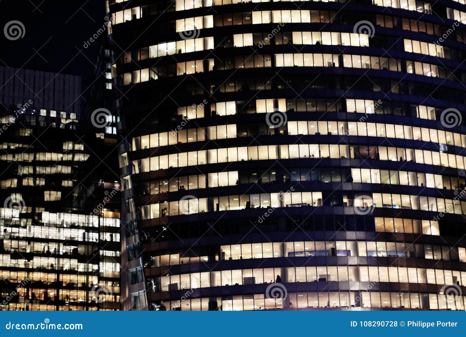 Paris kontorsbyggnadfönster på natten i affärsområdet