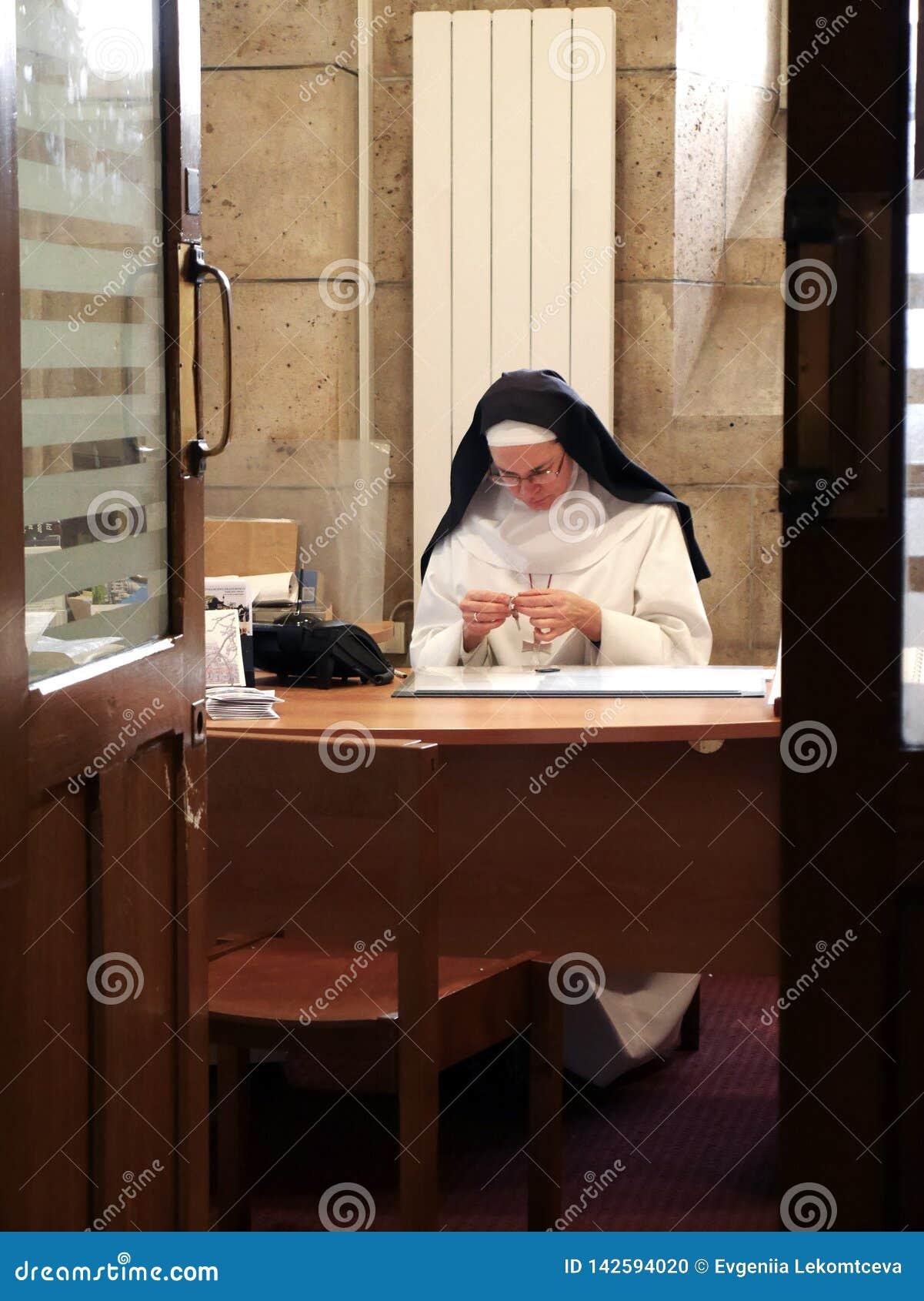 Paris, 6 Parvis Notre-Dame - Pl Jean-Paul II, Notre Dame Cathedral, am 20. Dezember 2018 Nonne, die am Tisch sitzt