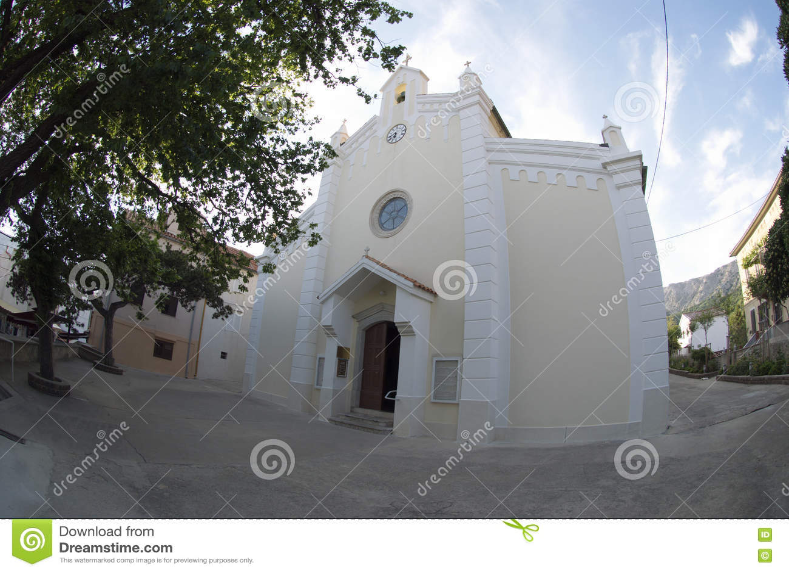 The parish church of St. Trinity and old tree in Baska on island Krk,Croatia