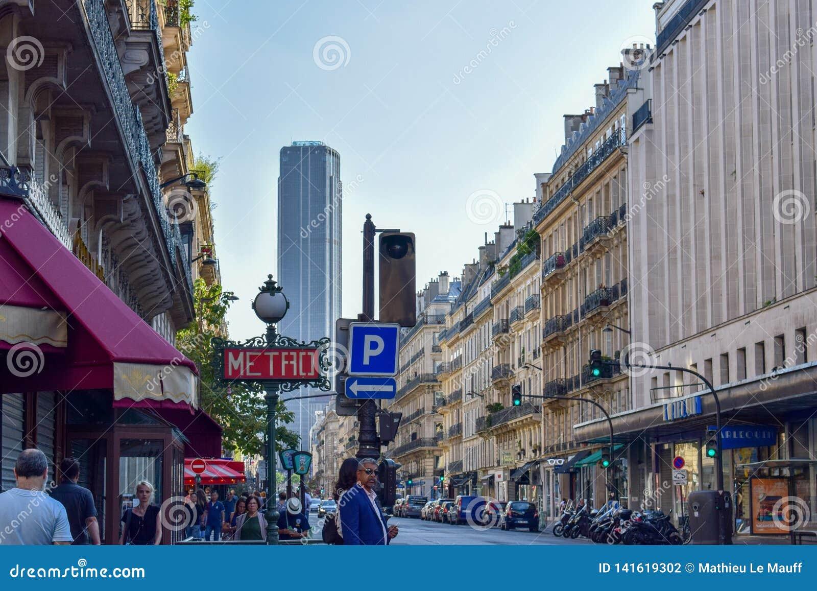 Parisisk gata med tunnelbanatecknet och Montparnasse torn i sommar