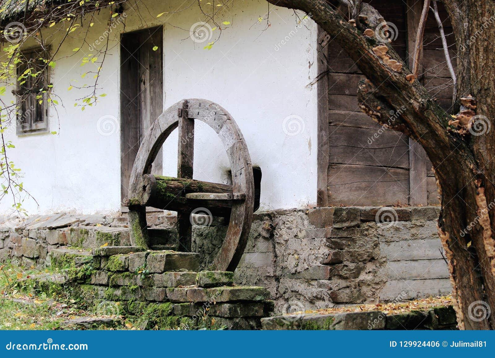 Park in de Oekraïne Een oud huis en een oude windmolen rijden dat pompenwater