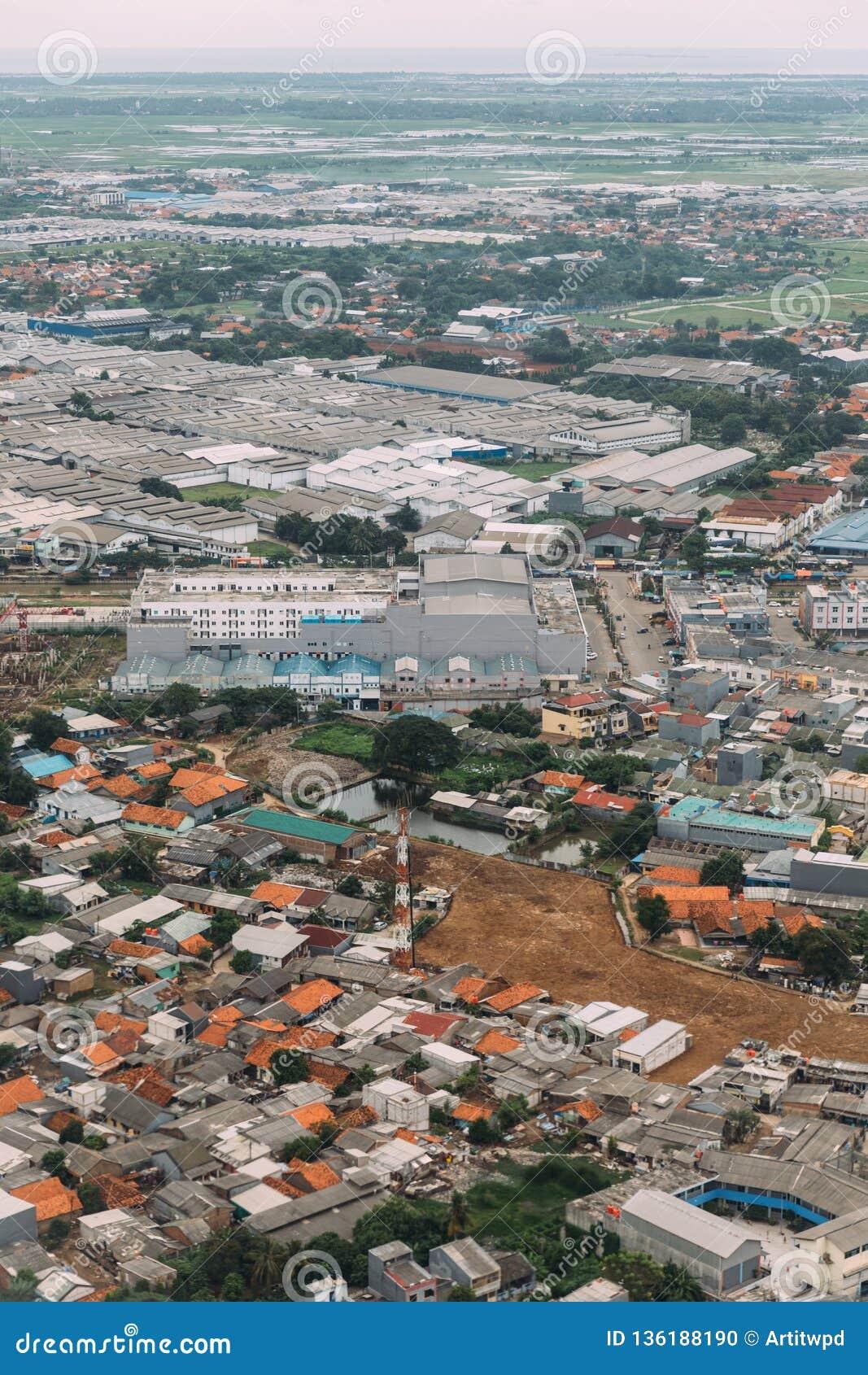 Park przemysłowy w poza śródmieściem Dżakarta, Indonezja Widok z lotu ptaka fabryki i domy od samolotu