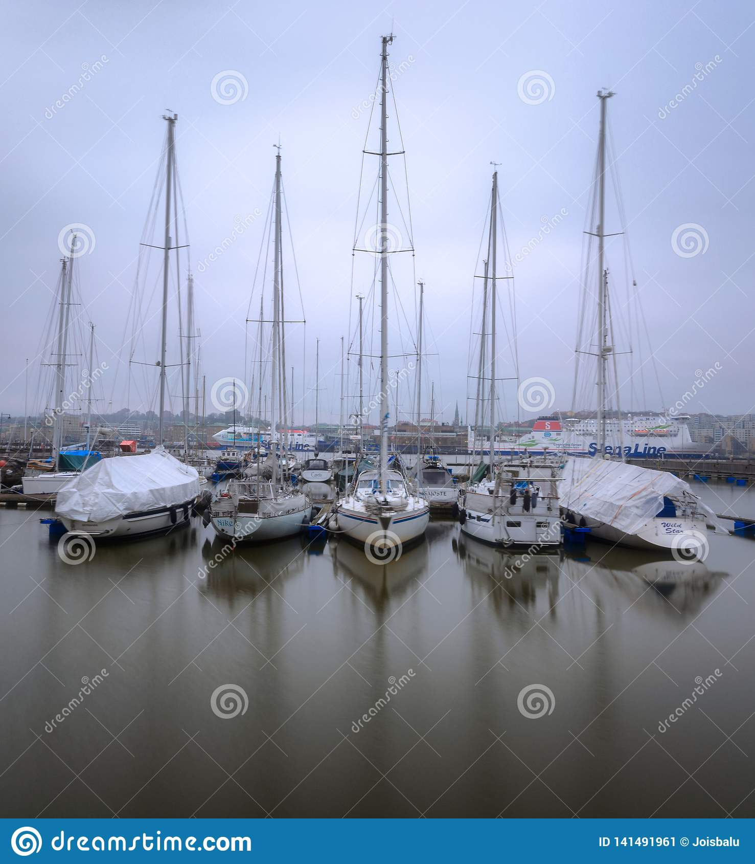 Parked boats in still water during a foggy morning