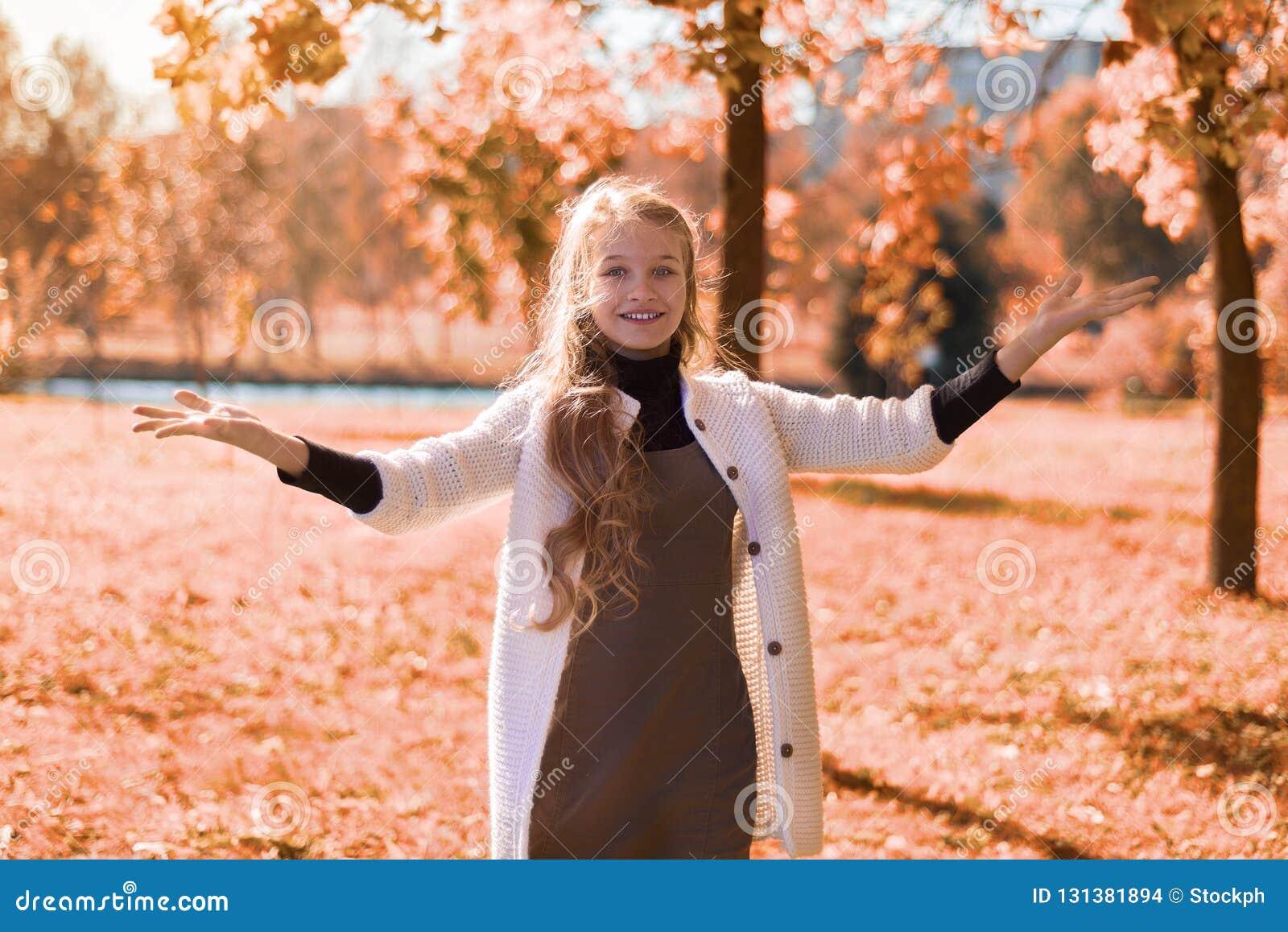 Parkerar den härliga ståenden för hösten av en ung flicka i med lövverk tonåringleenden och händer upp