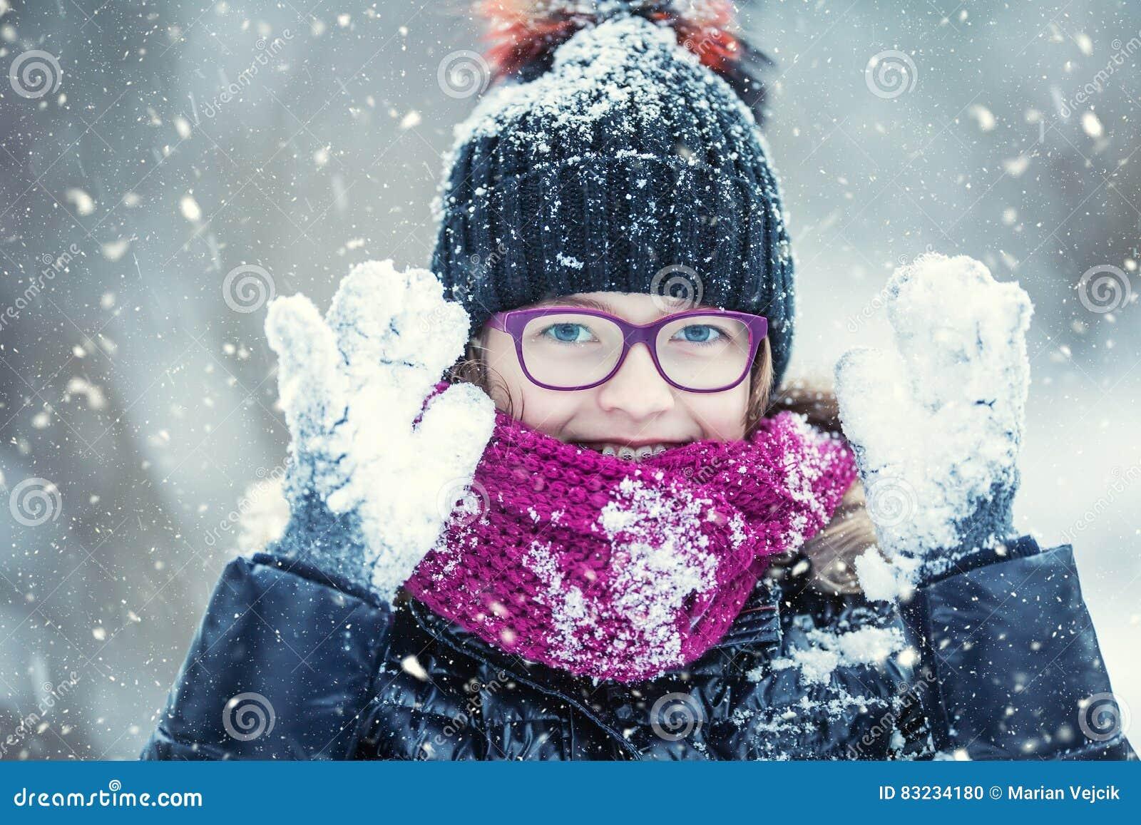 Parkerar den lyckliga flickan för skönhetvintern som blåser insnöad frostig vinter, eller utomhus Flicka och kallt väder för vint