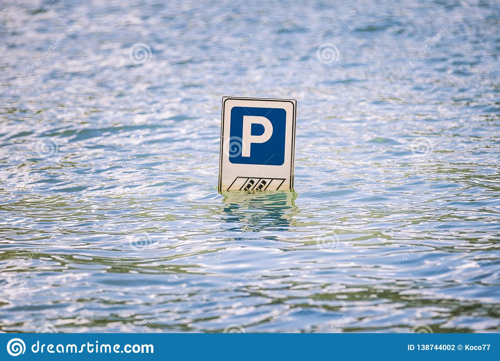 Parking cars road sign partially submerged in a flood.