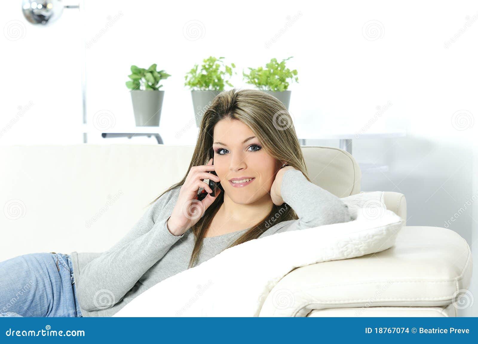 Giovane bella donna sul telefono in suo sofà