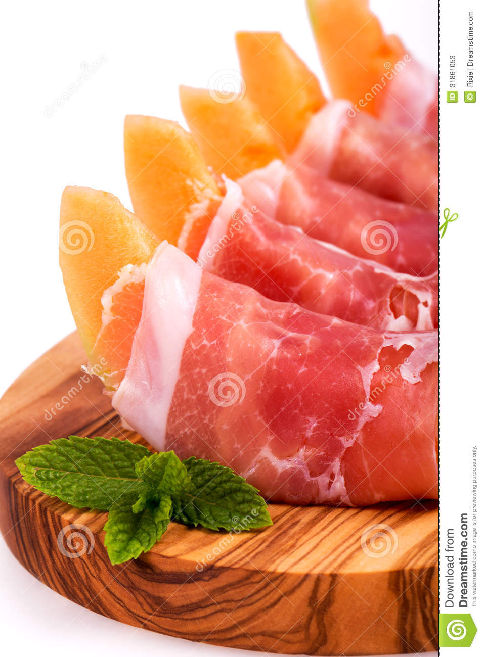 Parma ham and sliced melon starter served on olive wood board over ...