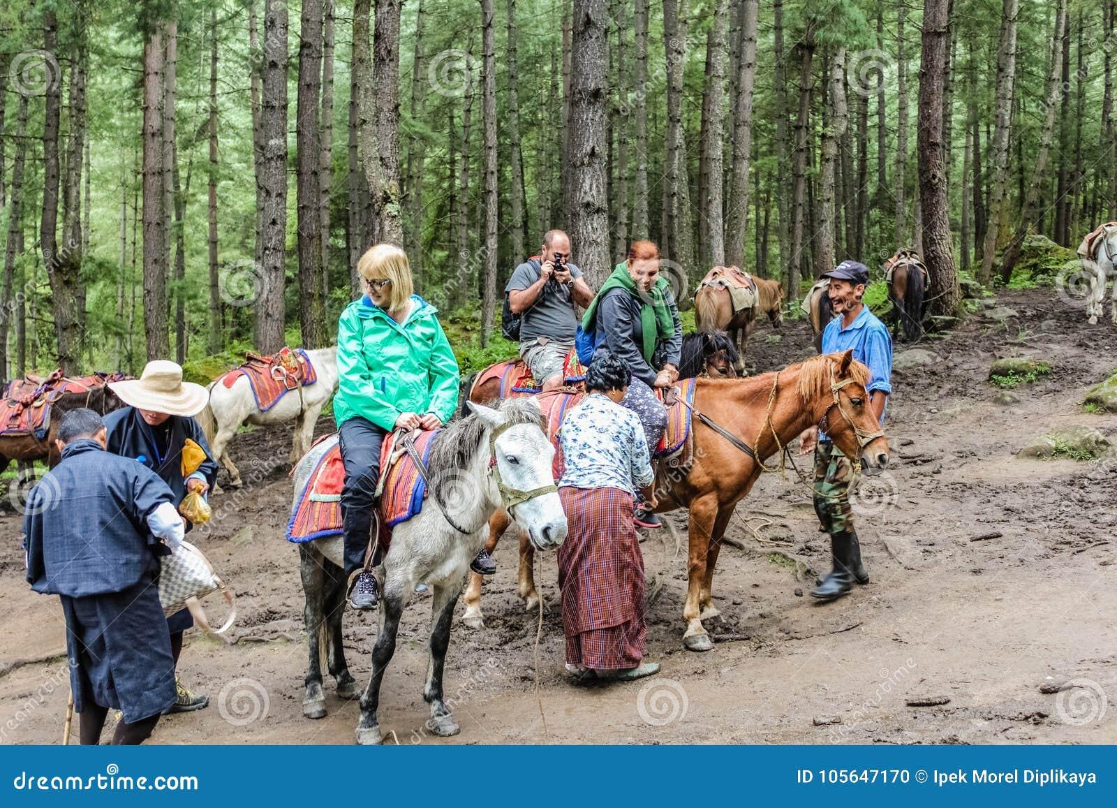 Paro Bhutan, Wrzesień, - 18, 2016: Turyści na koniach w kierunku Taktshang Palphug monasteru, Bhutan (tygrysa gniazdeczko)