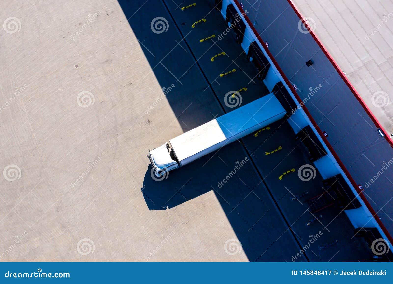 Parque de estacionamento da construção da logística de distribuição Silhueta do homem de neg?cio Cowering