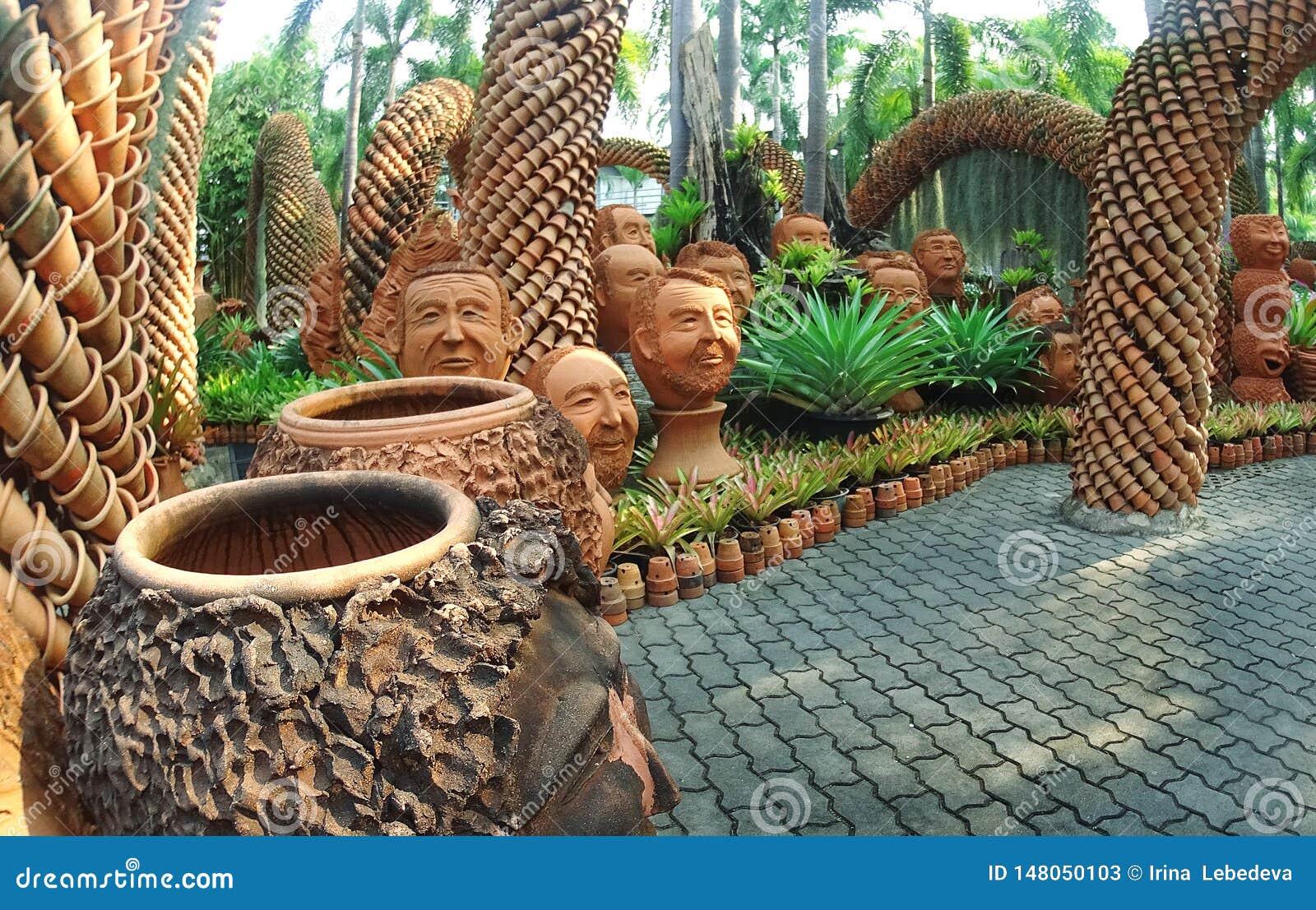 Parque tropical Nong Nooch en Pattaya con un diseño interesante del paisaje de potes de cerámica con las caras