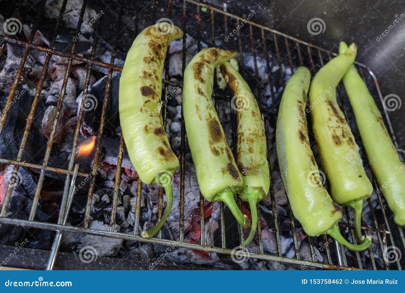 Parrilla de los chiles cuando suave él será fácil pelar Pimientas de chile frescas de anaheim que asan sobre un fuego del carb?n