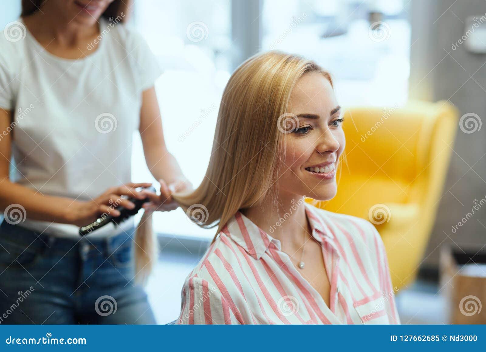 Parrucchiere che fa taglio di capelli per le donne nel salone di lavoro di parrucchiere